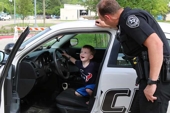 Happy Little Boy Inside Police Car