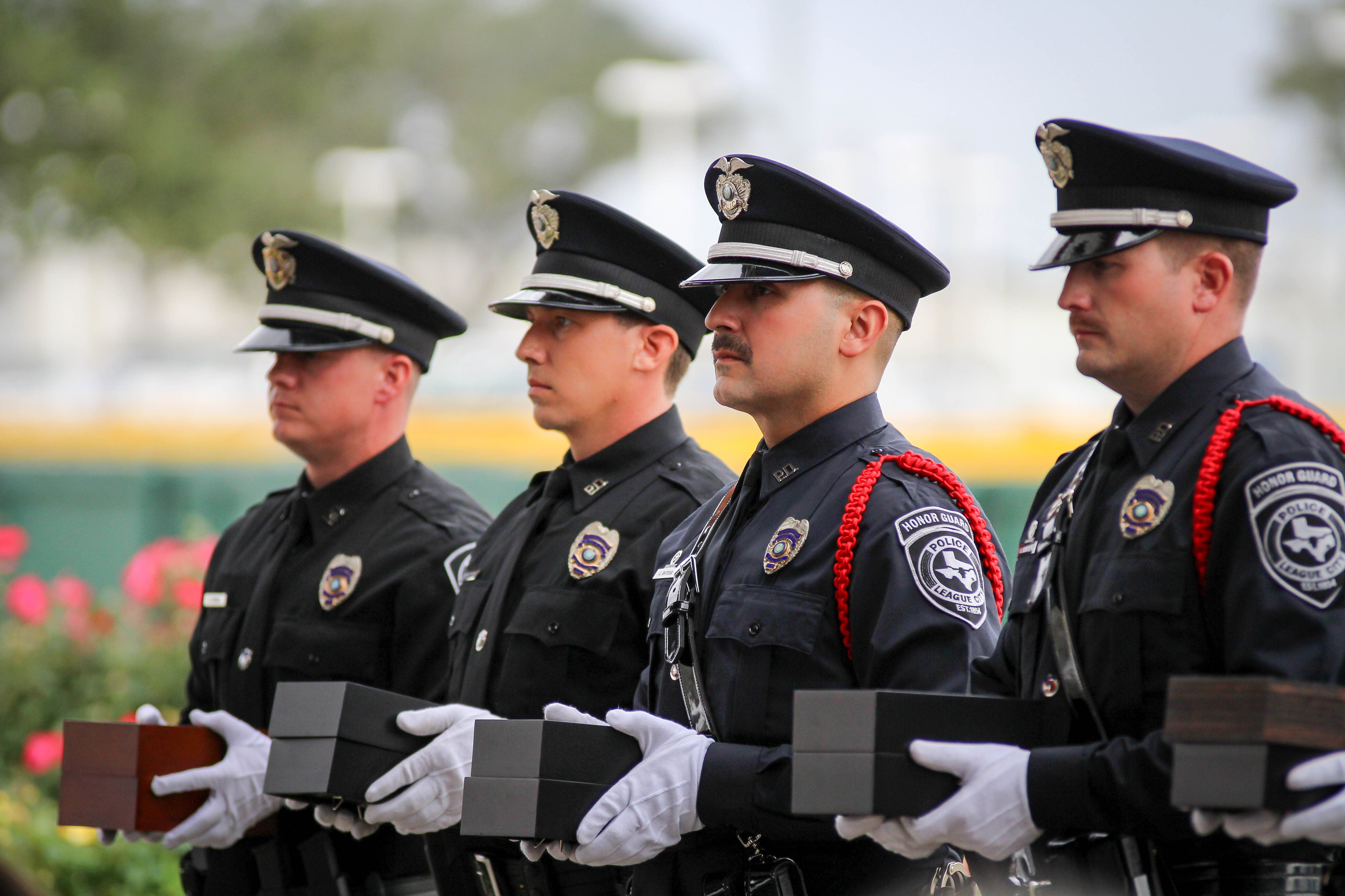 4 Police Men Standing in Dress Uniform Holding Boxes