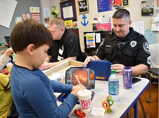 LCPD playing games with kids in classroom