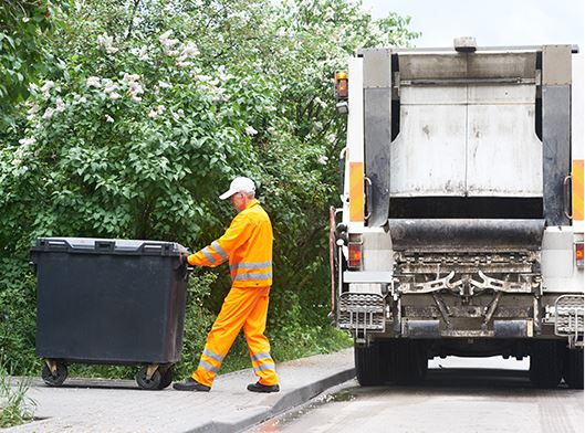 Man pushing trashcan on sidewalk by truck