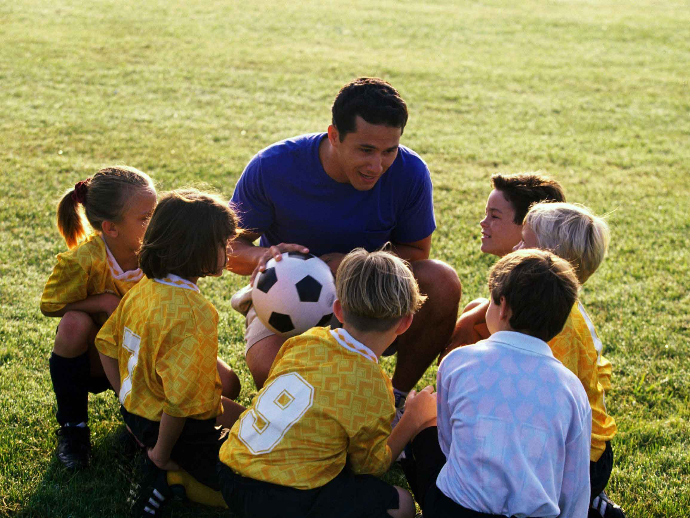 Soccer coach talking to children in yellow uniforms