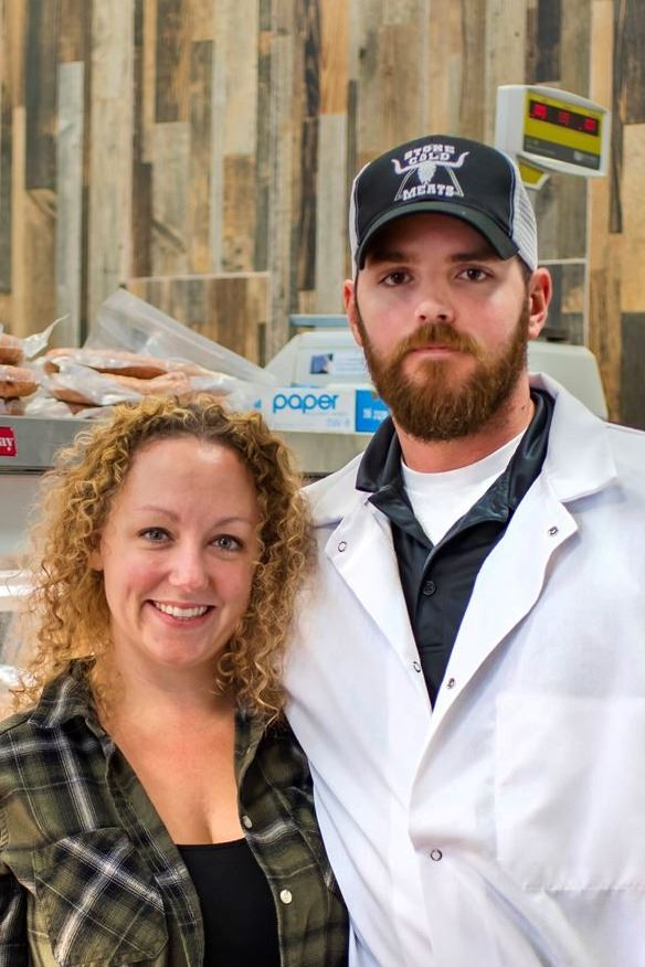 a couple posing in their butcher shop