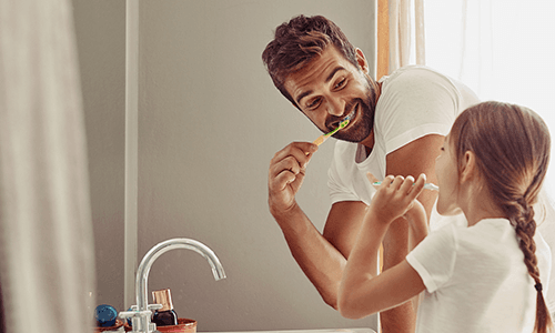 Father and daughter brushing their teeth while the faucet is off