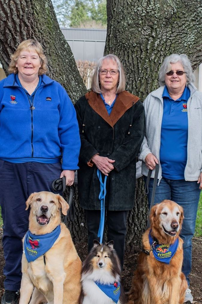 3 senior women posing with 3 dogs