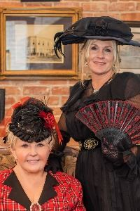 two women dressed in victorian clothes