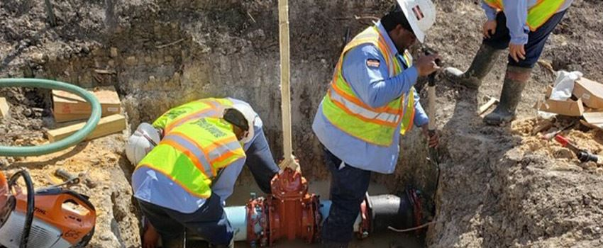Public works employees working on repairing a waterline inside a trench
