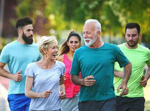 Group of mixed age people having a light jog at a local park