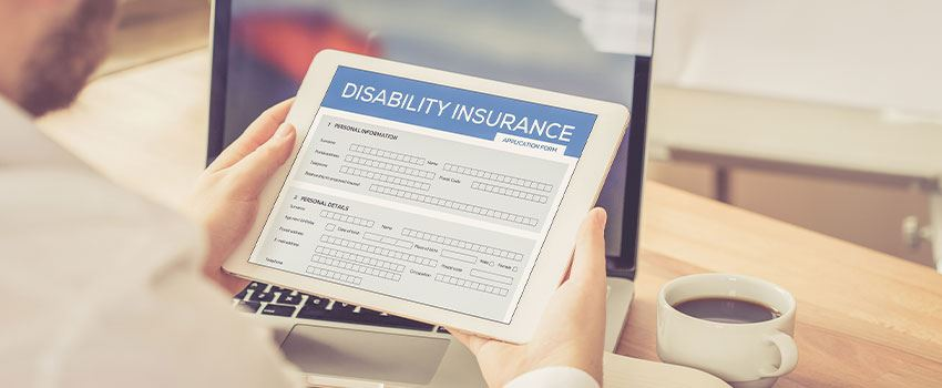 Man holding ipad and filling out online disability insurance form