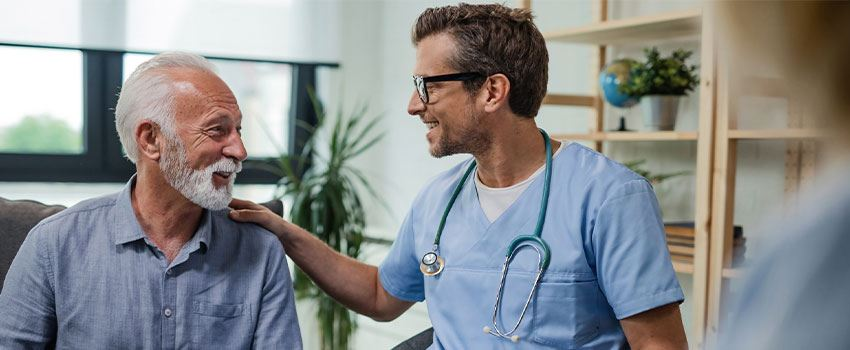 Happy doctor talking to senior male patient at home visit
