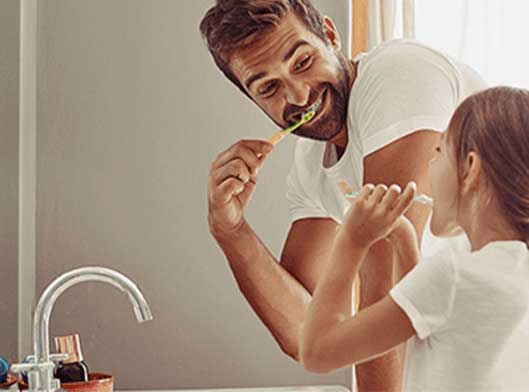 Father and daughter brushing their teeth while faucet is off