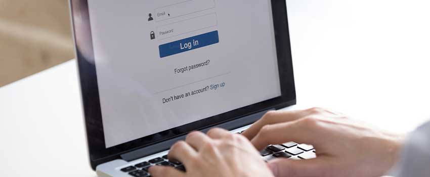 Person logging in to website on laptop
