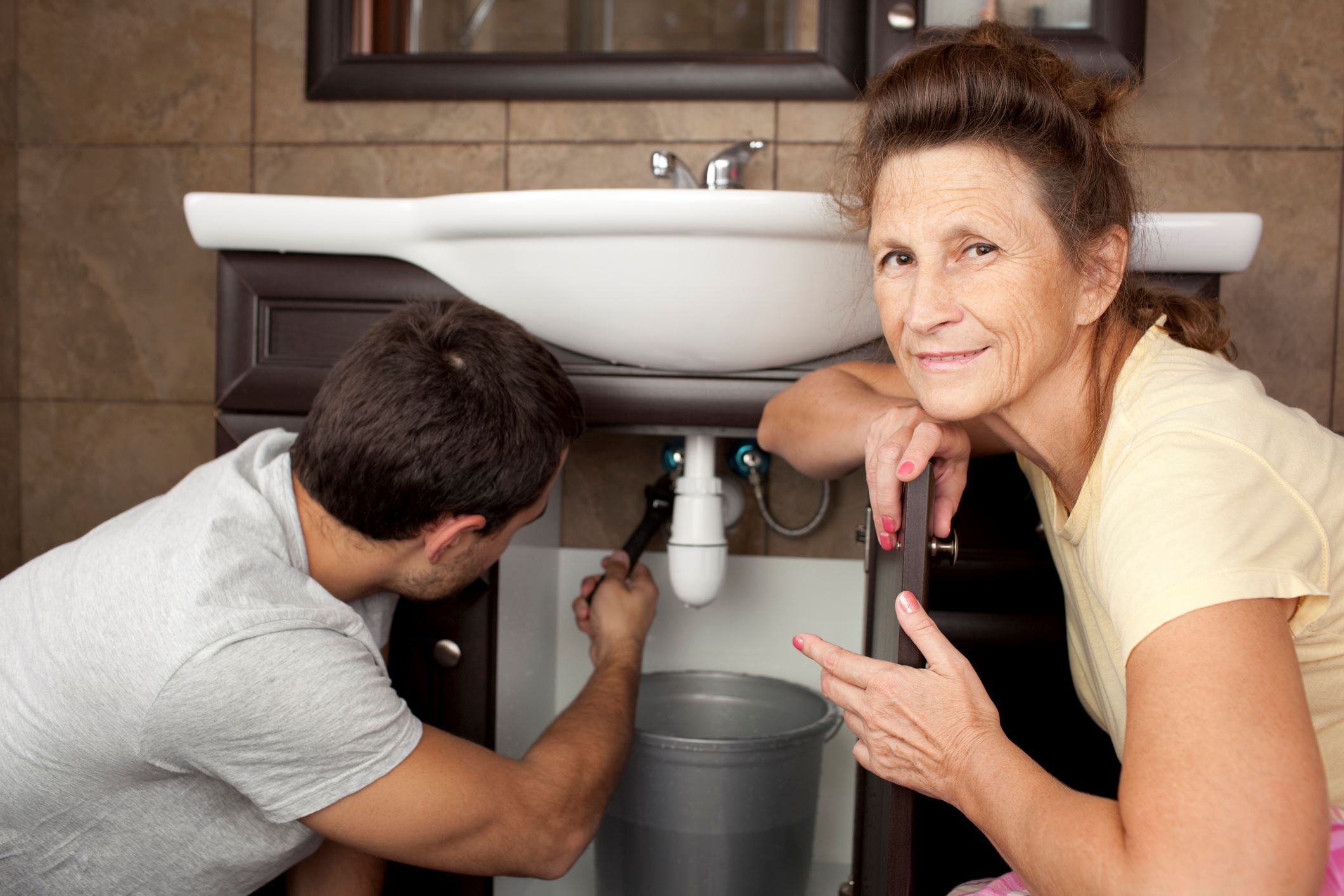 Lady watching plumber trying to fix leaky sink