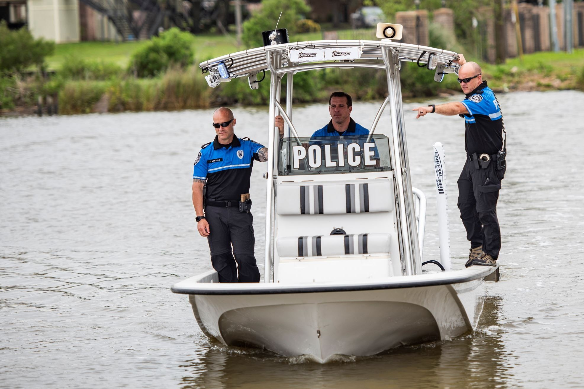 3 police officers on a boat