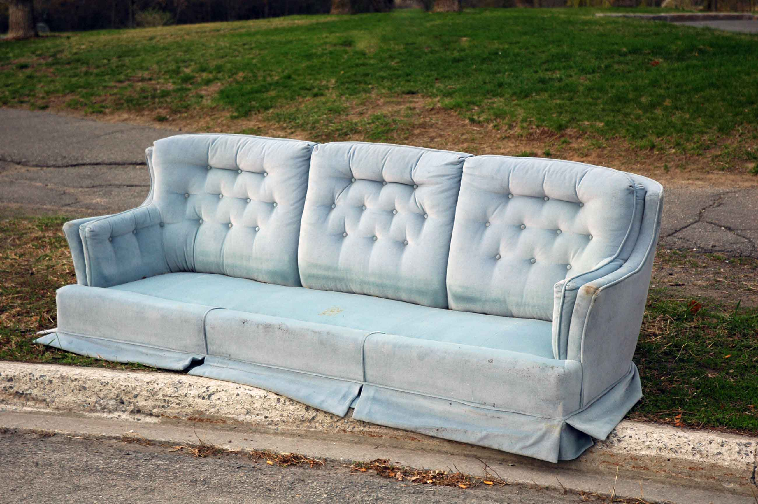 A couch on the curbside waiting to be picked up for trash